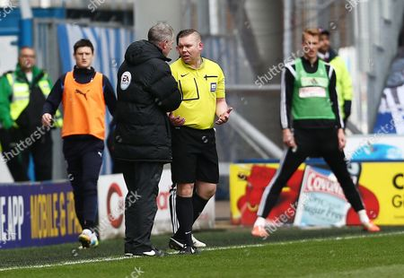 Referee Mr Richard Clark is given advise before he changed his mind over a sending off involving Cauley Woodrow and Shaun Hutchinson of Fulham