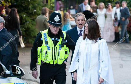 FROM ITVFROM ITV Emmerdale - Ep 7045 Friday 5 December  2014 It's the day of Ali Spencer [KELLI HOLLIS] and Ruby Haswell's [ALICYA EYO] wedding and Kerry is eager to start Ali's make up. But things go awry when Ali takes a call from the registry office saying they've cancelled the wedding, as the registrar has died. Ruby arrives to Ali and Dan trying to find another registry office. Harriet Finch [KATHERINE DOW-BLYTON] takes the plunge by suggesting they still have a blessing from her but later tells Ali they should just go the full hog, and have a proper wedding. But Ashley worries without the Bishop's permission Harriet will get into trouble.  Ruby and Ali walk down the aisle of the church with Sean Spencer [LUKE ROSKELL].  Soon there is more commotion when the police arrive at the church and everyone gathers as DI Bails [ROCKY MARSHALL] arrests the vicar Harriet.  Photographer -Amy Brammall This photograph is (C) ITV Plc and can only be reproduced for editorial purposes directly in connection with the programme or event mentioned above, or ITV plc. Once made available by ITV plc Picture Desk, this photograph can be reproduced once only up until the transmission [TX] date and no reproduction fee will be charged. Any subsequent usage may incur a fee. This photograph must not be manipulated [excluding basic cropping] in a manner which alters the visual appearance of the person photographed deemed detrimental or inappropriate by ITV plc Picture Desk. This photograph must not be syndicated to any other company, publication or website, or permanently archived, without the express written permission of ITV Plc Picture Desk. Full Terms and conditions are available on the website www.itvpictures.com TV Listings Magazines & websites Tuesday 25 November 2014, Newspapers Saturday 29 November 2014 Emmerdale - Ep 7045 Friday 5 December  2014 It's the day of Ali Spencer [KELLI HOLLIS] and Ruby Haswell's [ALICYA EYO] wedding and Kerry is eager to start Al