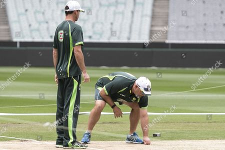 Australian coach Darren Lehman inspects the pitch with Greg Blewett ahead of their World Cup Final match against Australia at the Melbourne Cricket Ground.