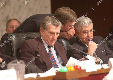 (L-R) Former Secretary of the Navy, John Lehman, unknown aide leaning over, Richard Ben Veniste, listen to CIA Director George Tenet testify.