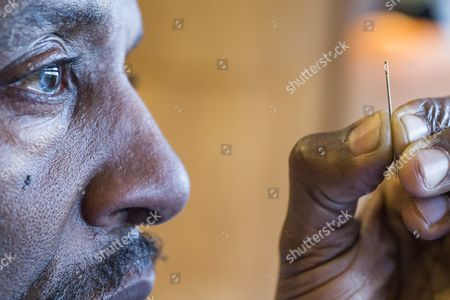 Willard Wigan looks at a piece of microscopic art in the eye of a needle