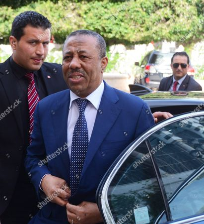 Prime Minister Abdullah al-Thinni (R) arrives at the Government Palace in Tunis