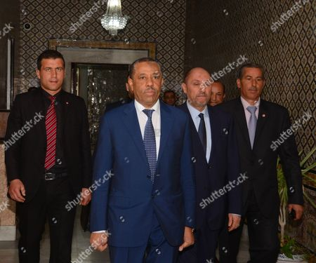 Prime Minister Abdullah al-Thinni (c) arrives at the Government Palace in Tunis