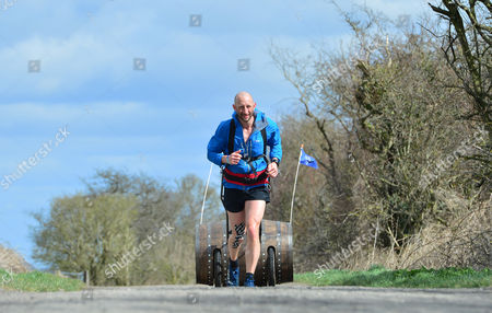 Rob Edmond running with a Bell's whisky barrel