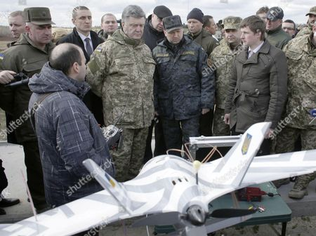 Ukrainian President Petro Poroshenko (CL) and Ukrainian secretary to the National Security and Defence Council Oleksandr Turchynov (CR) inspect weapons and military equipment as they visit the training centre of the Ukrainian National Guard