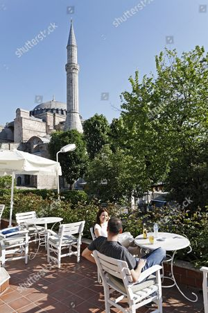 Stock Photo of Young couple resting in a café with terrace overlooking the Hagia Sophia, Sultanahmet, Istanbul, Turkey