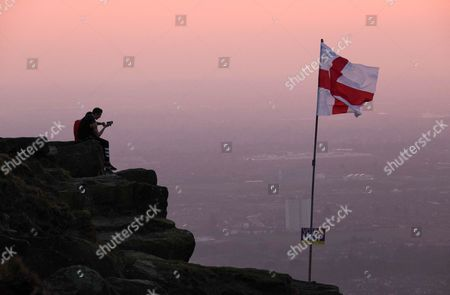 Two men sit on a rocky outcrop next to a St George flag with a placard attached showing support for UKIP on the top of local landmark, Eston Nab on Teesside ahead of the General Election on May 7