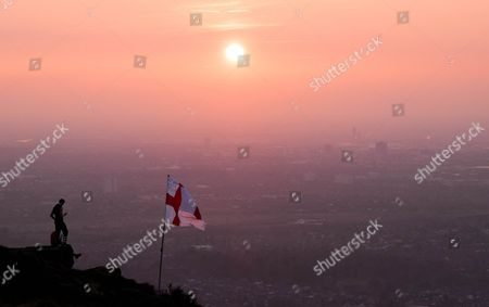 A man stands on a rocky outcrop next to a St George flag and looks out over the industrial and residential areas of Teesside from an area known as Eston Nab as smog hangs in the air as the sky glows orange during a dramatic sunset.