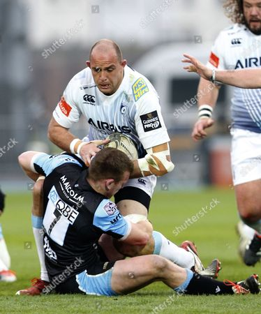 Chris Fusaro of Glasgow Warriors tackles Lou Reed of Cardiff Blues