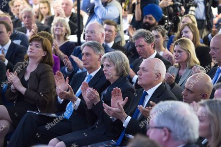 L to R Front: Nicky Morgan, Philip Hammond, Theresa May and Iain Duncan Smith. Rear: Eric Pickles, Oliver Letwin and Justine Greening. Member soft the British government cabinet listen to British prime minister David Cameron speaking at UTC