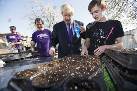 Mayor of London Boris Johnson potting seeds at Cultivate Urban Farm while campaigning for the conservative party in Acton, West London with local conservative candidate Angie Bray (not pictured).