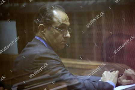 Gamal Mubarak, the son of former former the President sits in a courtroom cage during his retrial