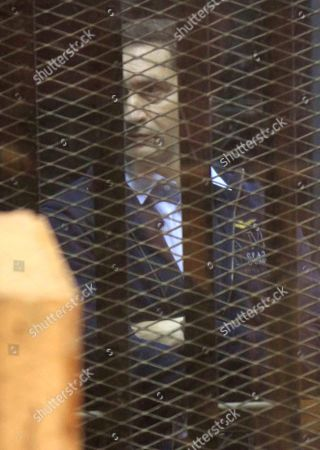 Alaa Mubarak, the son of former former the President sits in a courtroom cage during his retrial
