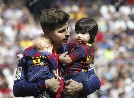 Stock Photo of Gerard Pique holds his two sons Milan Pique Mebarak (R) and Sasha Pique Mebarak (L)