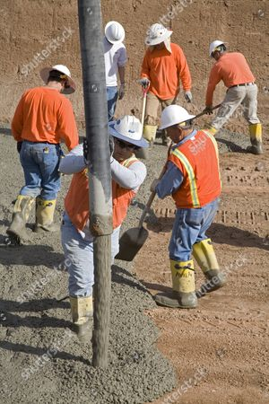 Workers line a Salt River Project canal with concrete to cut down on water loss; the city's water supply comes largely from canals that bring water from the surrounding mountains and from the Colorado River, Phoenix, Arizona, USA