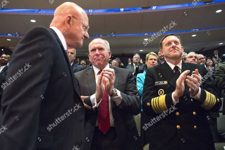 CIA Director John O. Brennan and Director of the National Security Agency Mike Rogers applaud as Director of National Intelligence James Clapper takes his seat