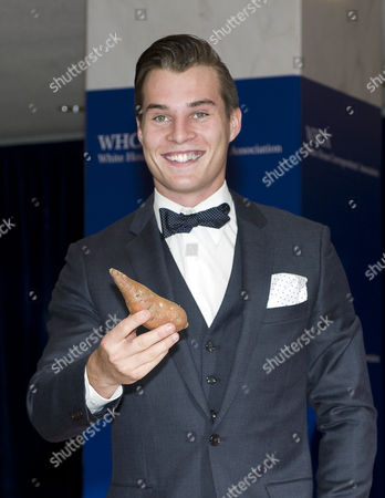 Stock Image of Marcus Johns poses with a sweet potato as he