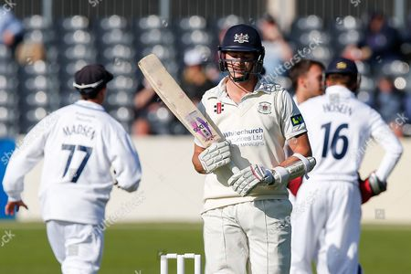 James Hughes of Gloucestershire walks after he is bowled L.B.W. for 6 by Alex Hughes of Derbyshire