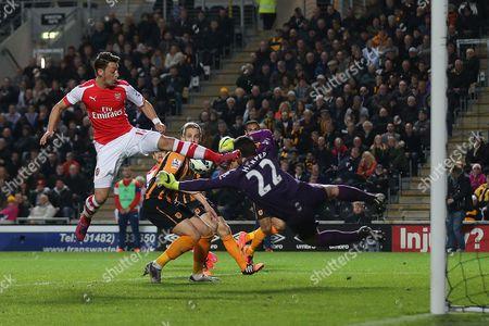Steve Harper of Hull City dives to prevent the ball reaching Mesut Ozil of Arsenal