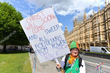 Stock Photo of Neil Horan, the 'Dancing Priest', holding one of his banners outside Parliament on polling day