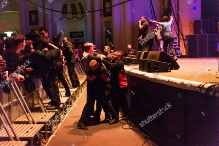 Audience members struggle with security staff as dozens invade the stage at Brixton Academy, after they were encouraged to do so by the performing musical artist Jay Electronica seen onstage, supporting Tim Barnwell Flying Lotus.