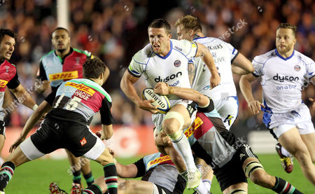 Sam Burgess of Bath Rugby drives towards Harlequins' Ollie Lindsay-Hague (L)