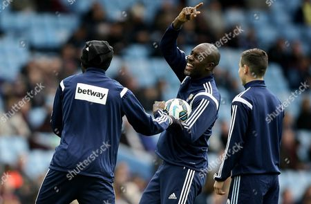 Carlton Cole of West Ham United jokes with Alex Song of West Ham United