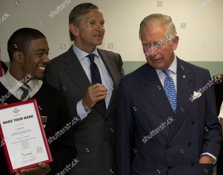 Britain's Prince Charles glances across after handing out a certificate to Prince's Trust 'Mark your Mark participant Reon Bryan, left, during a visit to British retailer Marks and Spencer, as CEO Marc Bolland at center looks on, in London