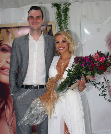 Dani Mathers on stage at the Manshion with Cooper Hefner (son of Hugh) who presented; her with flowers and cheque for $100000