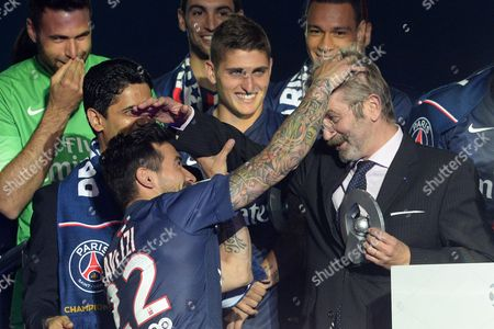 PSG player's Ezequiel Lavezzi (L) celebrates its French championship with the LFP president's Frederic Thiriez at the end of the Football French Championship game