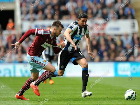 Jonas Gutierrez of Newcastle United chases down the ball with Carl Jenkinson of West Ham United