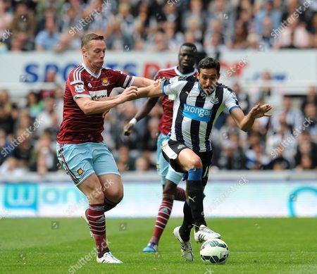 Kevin Nolan of West Ham United (left) challenges Jonas Gutierrez of Newcastle United