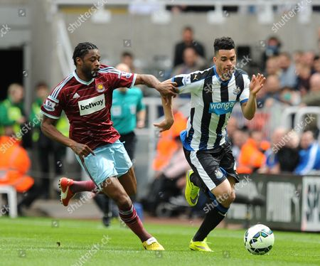 Alexandre Song of West Ham United (left) challenges Emmanuel Riviere of Newcastle United
