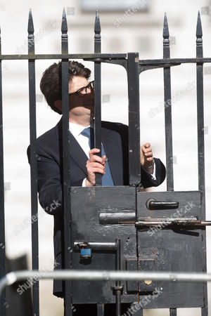 Political advisor Andrew Feldman struggles to get through the gates as he arrives