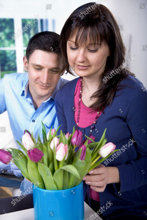 Stock Picture of MODEL RELEASED Young couple looking at tulips in a vase