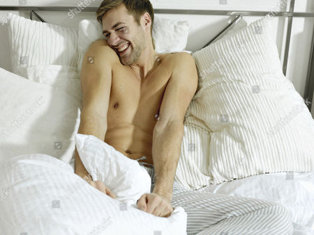 MODEL RELEASED Charming bare chested man wearing pyjamas sitting on a bed, smiling