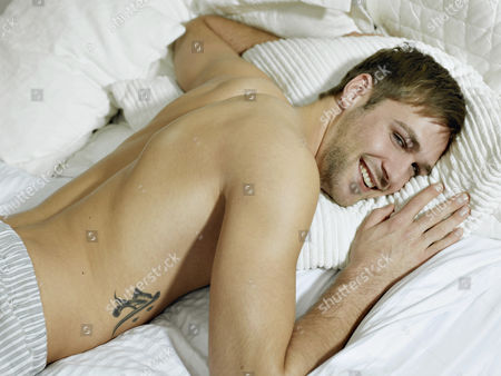 MODEL RELEASED Charming bare chested man wearing pyjamas lying in bed, smiling