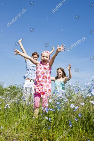 MODEL RELEASED A mother and her two daughters running joyfully across a flower meadow