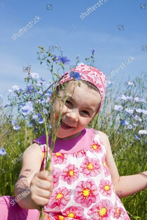 MODEL RELEASED Girl standing in a flower meadow with a bouquet of flowers