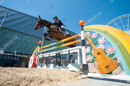 """Olympic Gold Medalist Peter Charles jumps Douglas Delight over the London 2012 """"Abbey Road"""" fence in front of the Echo Arena, Liverpool to launch the inaugural Liverpool International Horse Show to take place 1-3 January 2016"""