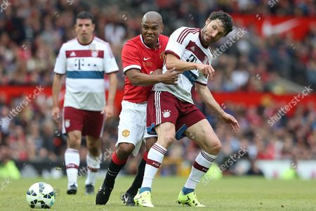 Quinton Fortune of Manchester United Legends competes with Mark Van Bommel of Bayern Munich All Stars at the Manchester United Legends v Bayern Munich All Stars match