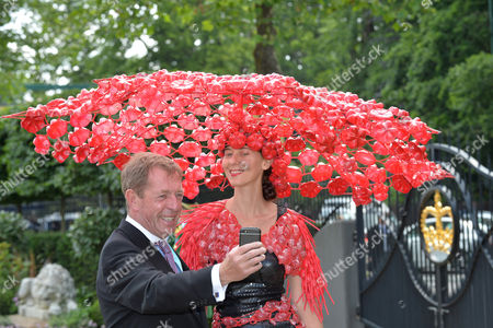 TV presenter Derek Thompson takes a selfie with a racegoer as she arrives for Ladies Day