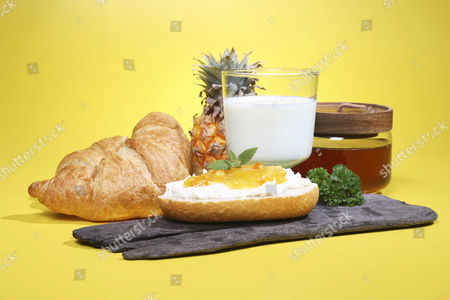 Breakfast containing cream cheese, honey and a glass of milk