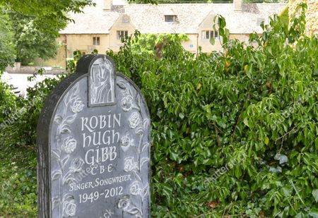 New marble headstone at the grave of Robin Gibb with his home in the background