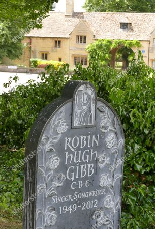 Stock Image of New marble headstone at the grave of Robin Gibb with his home in the background