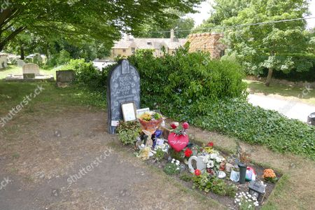 Stock Picture of New marble headstone at the grave of Robin Gibb with his home in the background