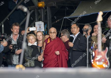 The Dalai Lama (Emily Eavis on his immediate left) watching Patti Smith perform on the Pyramid Stage