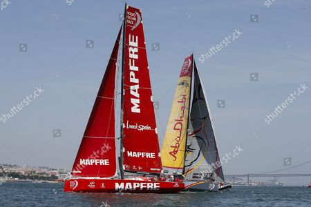 MAFRE Team skippered by Iker Martinez from Spain and Abu Dhabi Ocean Racing team skippered by Ian Walker from United Kingdom, sail down the Tagus River, in the Oeiras In-Port Race in Lisbon on June 6, 2015, on the eve of Leg 8 between Lisbon and Loirent, France.