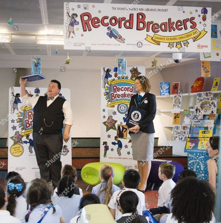 Stock Picture of Craig Glenday the editor of the Guiness World Records Book and his team present 'My Pledge to be a Record Breaker' to children of the third year of St. Johns Catholic School, at at Record Breakers - Hosted by Canada Water Library and the Reading Agency.