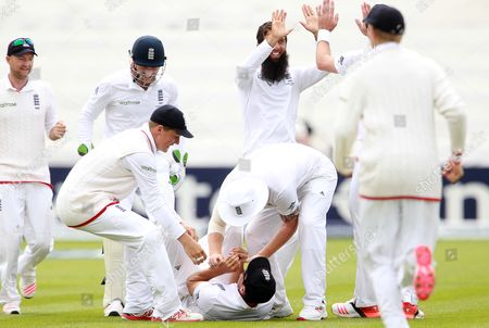 Moeen Ali celebrates with team mates after Alastair Cook catches Brad Haddin of Australia.